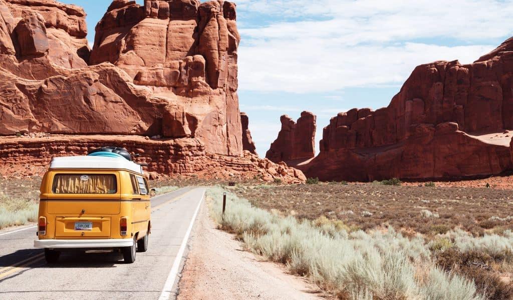 A bus navigates betwixt two mountain ranges