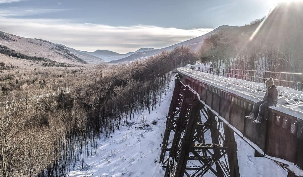 A tourist overlooks a snowy scene while sitting on a disused bridge