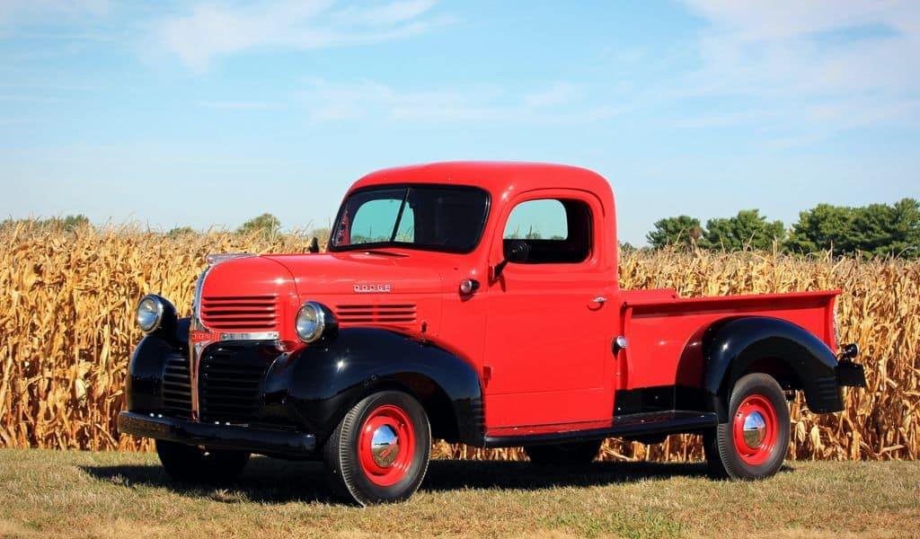A red truck stands before a corn field