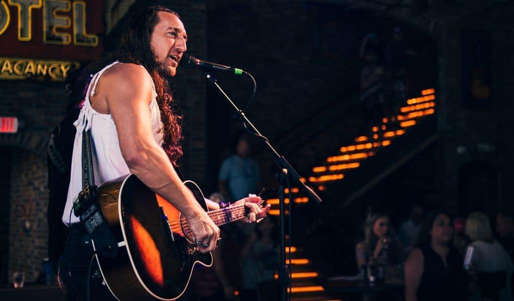 Rock country singer stands at microphone, strums guitar, while on stage in Tennessee
