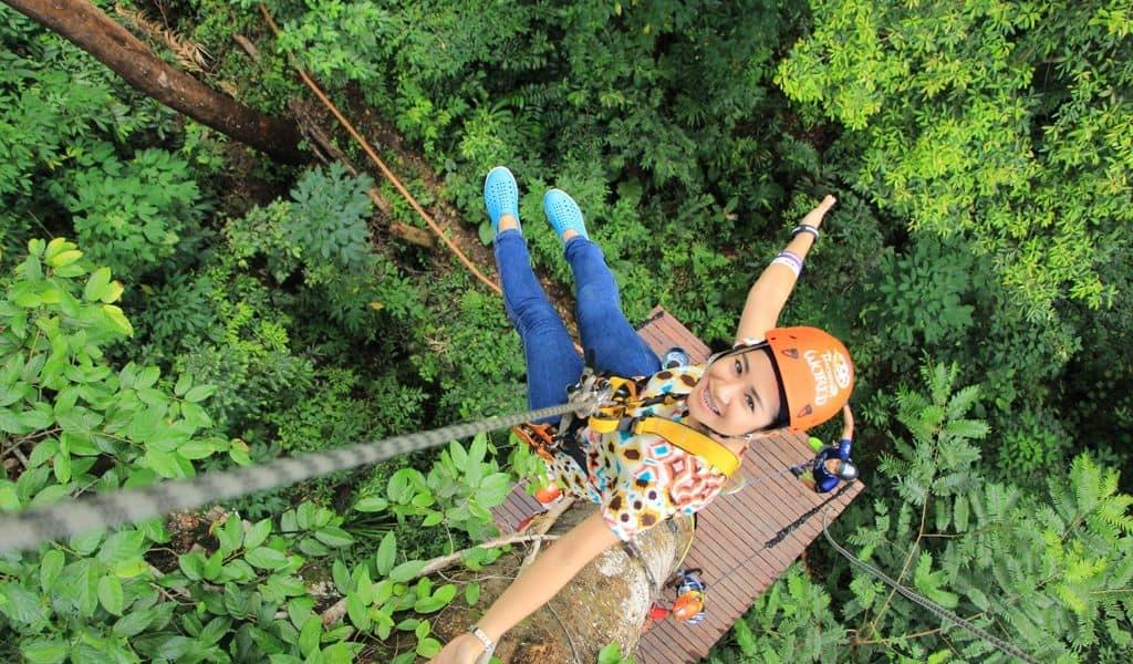 Woman wearing orange helmet strapped into ziplining equipment over a luscious forest.