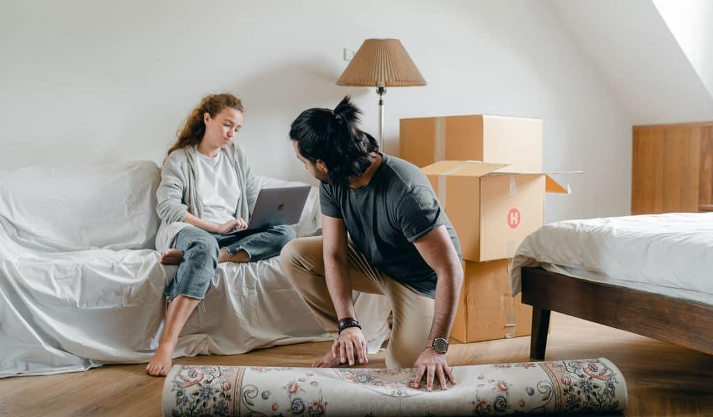 A couple packing while searching for moving company reviews