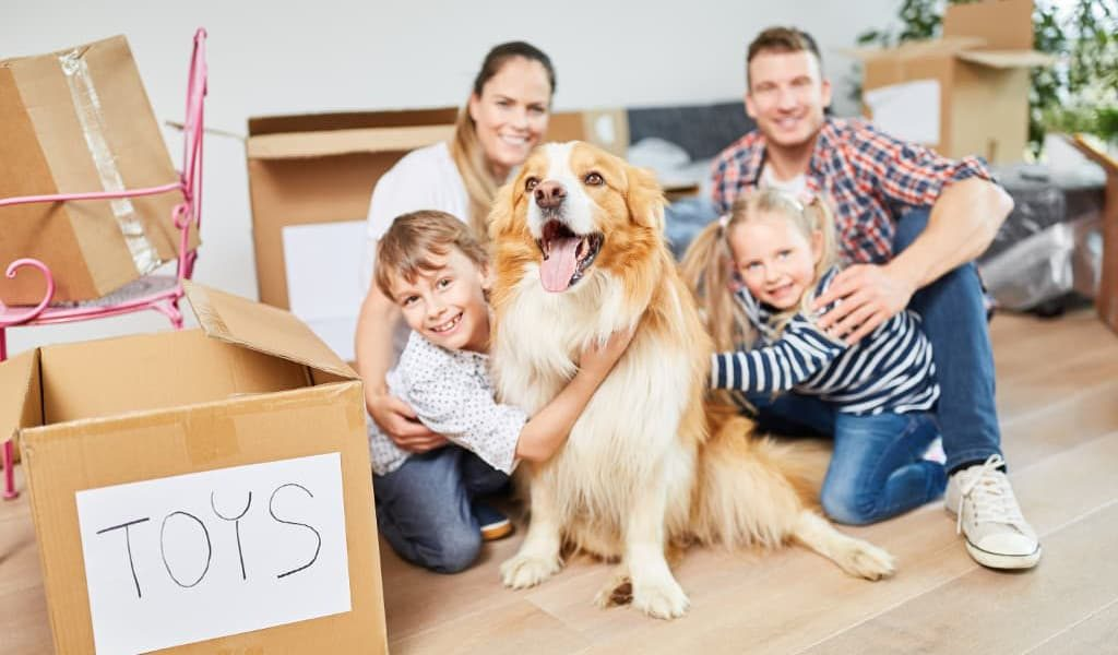 A happy family and their pet dog with unpacked moving boxes