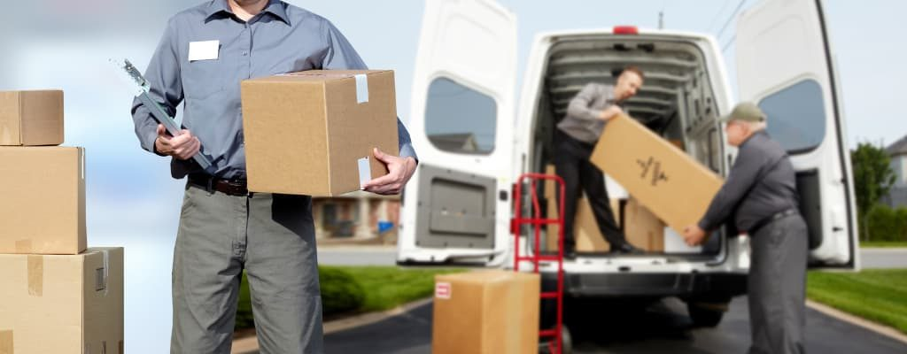 Professional movers helping pack things in truck
