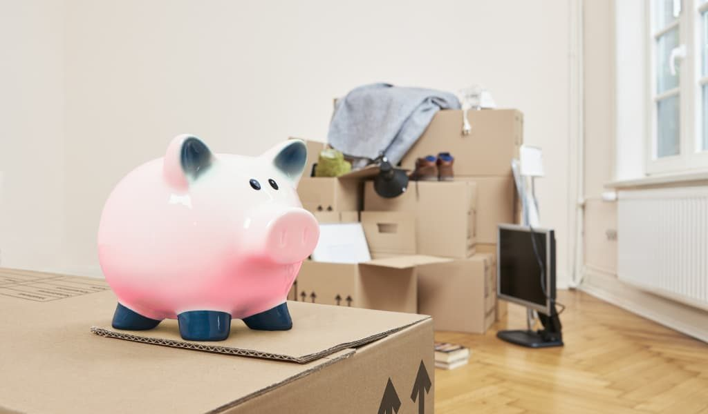 Piggy bank savings on top of moving boxes