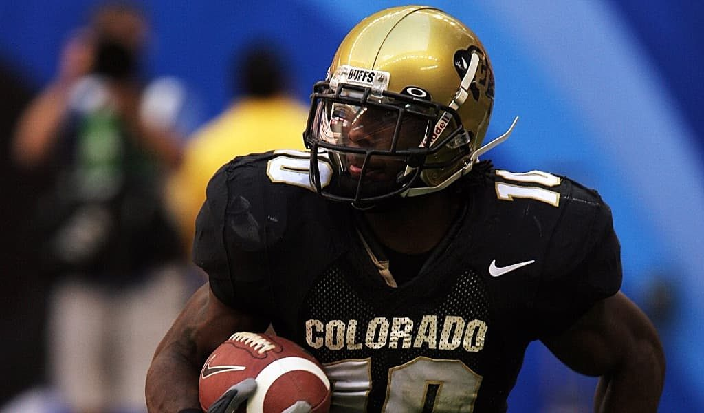 Colorado football player wearing black jersey and golden helmet while carrying a football on the field