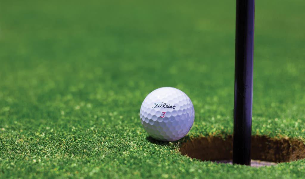 White golf ball beside hole on green grass