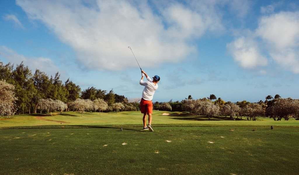 Man wearing white shirt swinging golf club on a green, luscious golf course