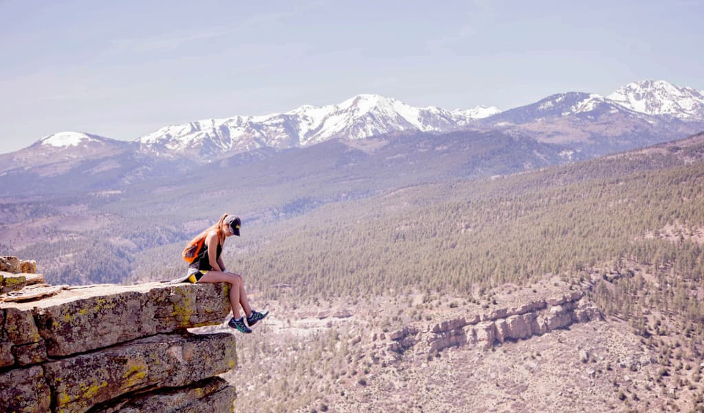 Female hiker sitting on a ledge overlooking the valley with mountains in the background