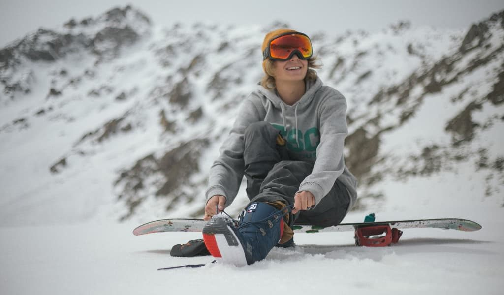 Woman wearing a grey hoodie sitting on a snowboard surrounded by snow