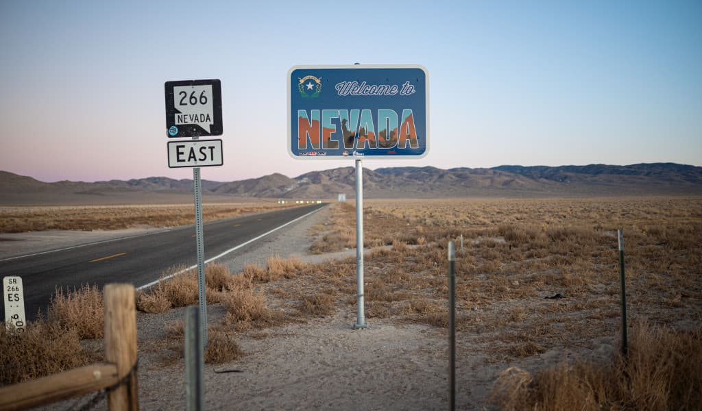Blue 'Welcome to Nevada Sign' beside the main highway with mountains in the background