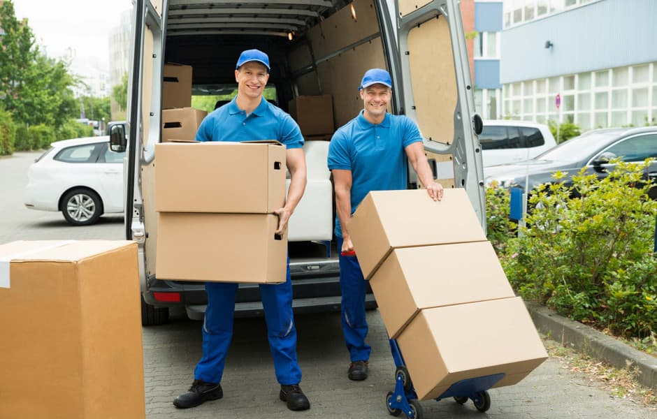 Professional movers in blue uniforms carrying a couch into a van
