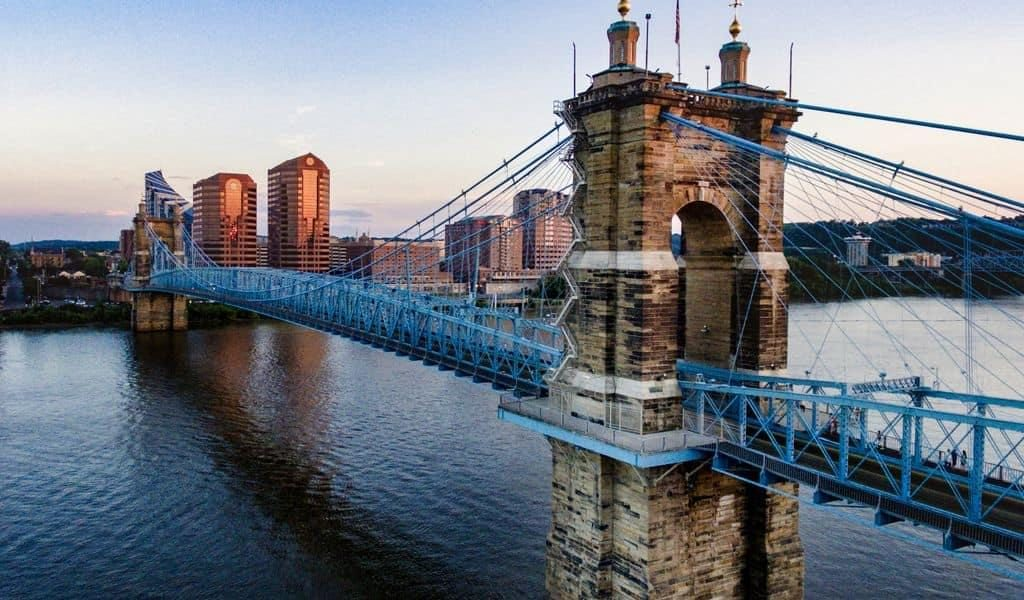 A blue bridge going across a river near Cincinnati, OH