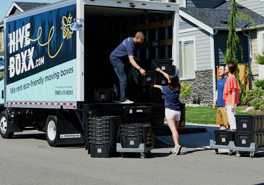 Two movers load up a truck, while the homeowners watch excitedly.