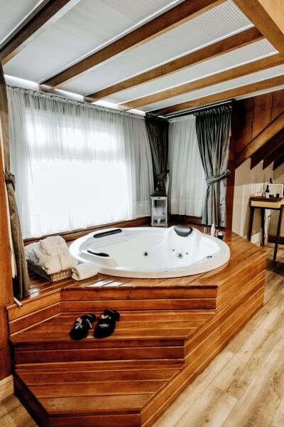 White wooden hot tub atop a tiered wooden spa
