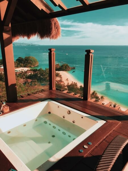 Inset hot tub in a wooden porch above a teal sea