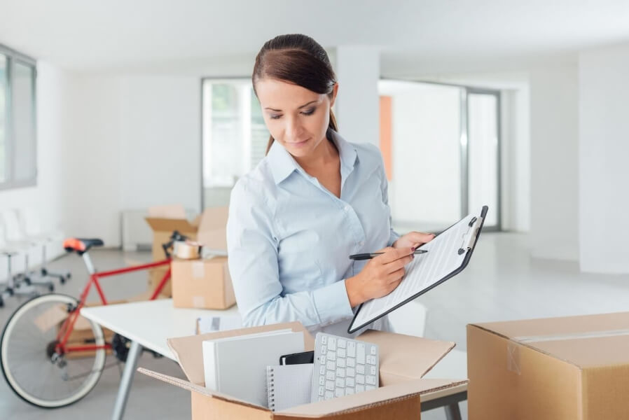 Woman checking over packed business boxes