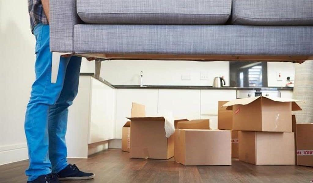 A man in jeans is picking up a grey couch; moving boxes are in the background