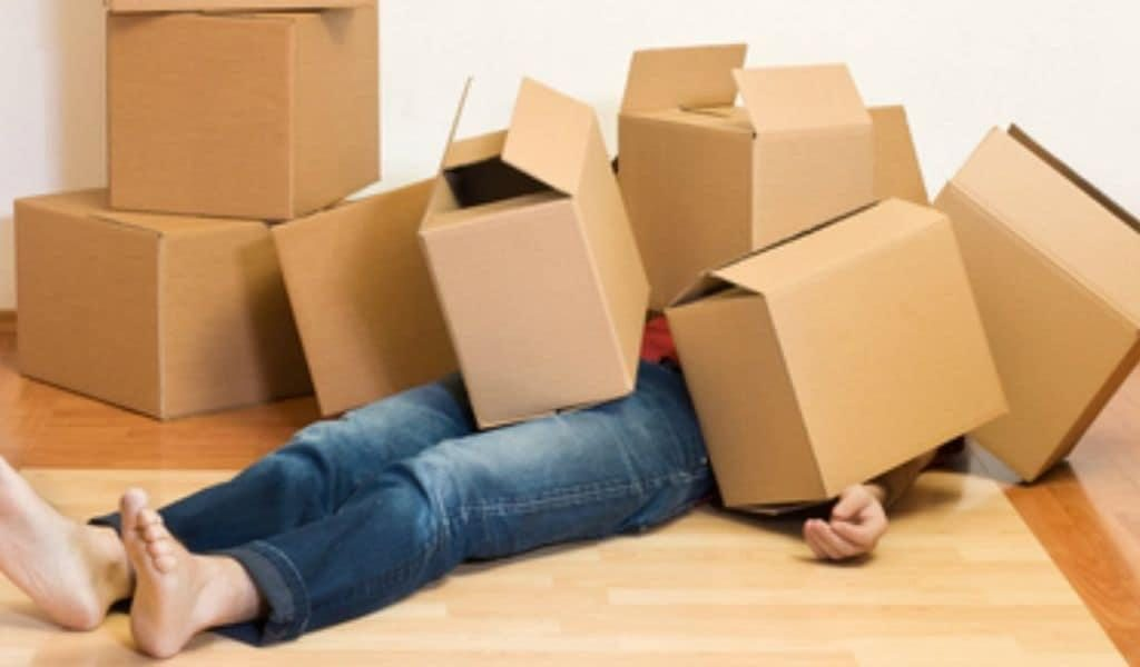 A person lies on the ground, completely covered by a stack of cardboard moving boxes
