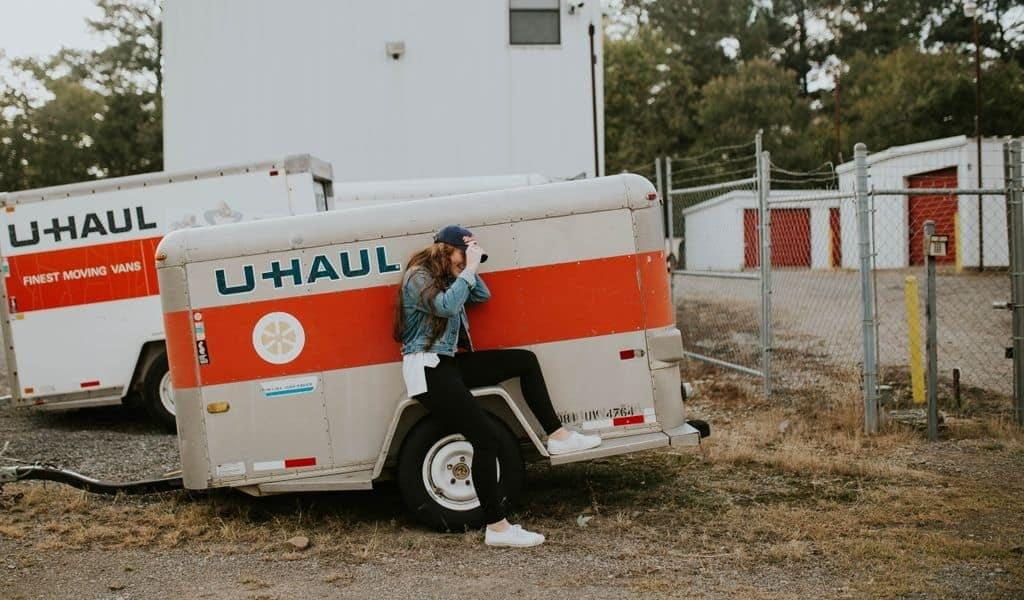 A woman in black leggings and a denim jacket sits on the wheel of a U-Haul trailer